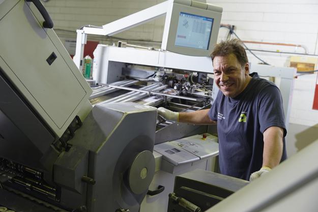 Advance Press staff member running folding machine at Perth factory